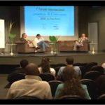 Foto de um salão com pessoas sentadas observando três pessoas em cima de um palco, essas três pessoas estão interagindo entre si e estão sentadas em sofás diferentes.