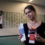 Foto de uma mulher segurando um panfleto e um presenta do Instituto Alana.