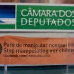 Imagem com um banner laranja dentro da câmara dos deputados descreve: Pare de manipular nossas crianças. Stop manipulating our chidren.