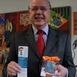 Foto de Luiz Carlos Hauly segurando um panfleto e um presente do Instituto Alana.
