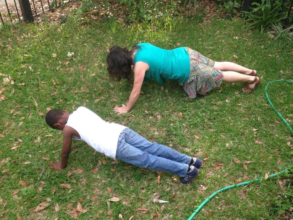 Foto de uma mulher e um garoto fazendo flexão em um pátio.