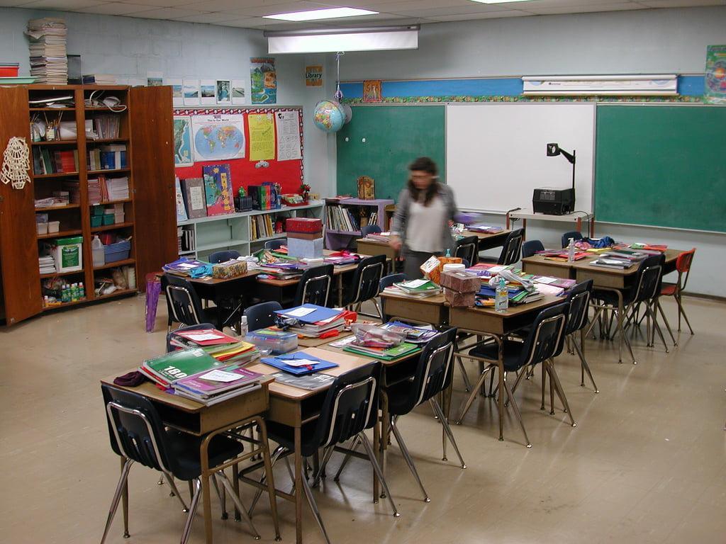 Imagem de uma sala de aula, uma pessoa caminha entre as carteiras.