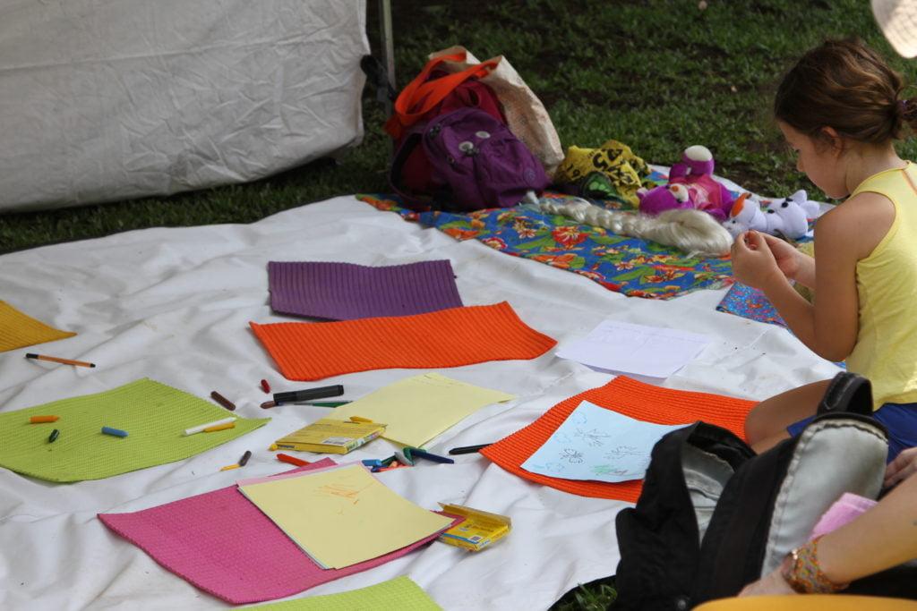 Na foto uma criança desenha sentada no chão onde estão várias esteiras e giz de cera.