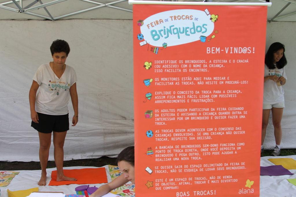 Um cartaz com os combinados da Feira de Trocas de Brinquedos e no fundo um pessoa em pé.