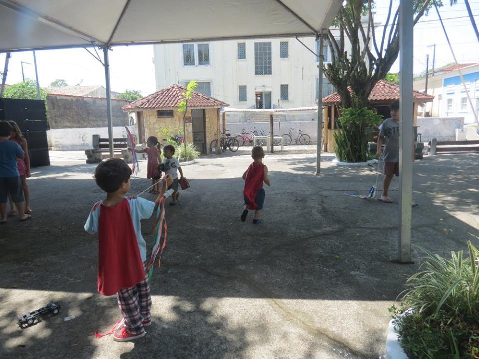 Crianças com capas vermelhas estão em uma praça ao ar livre e brincam com fios coloridos