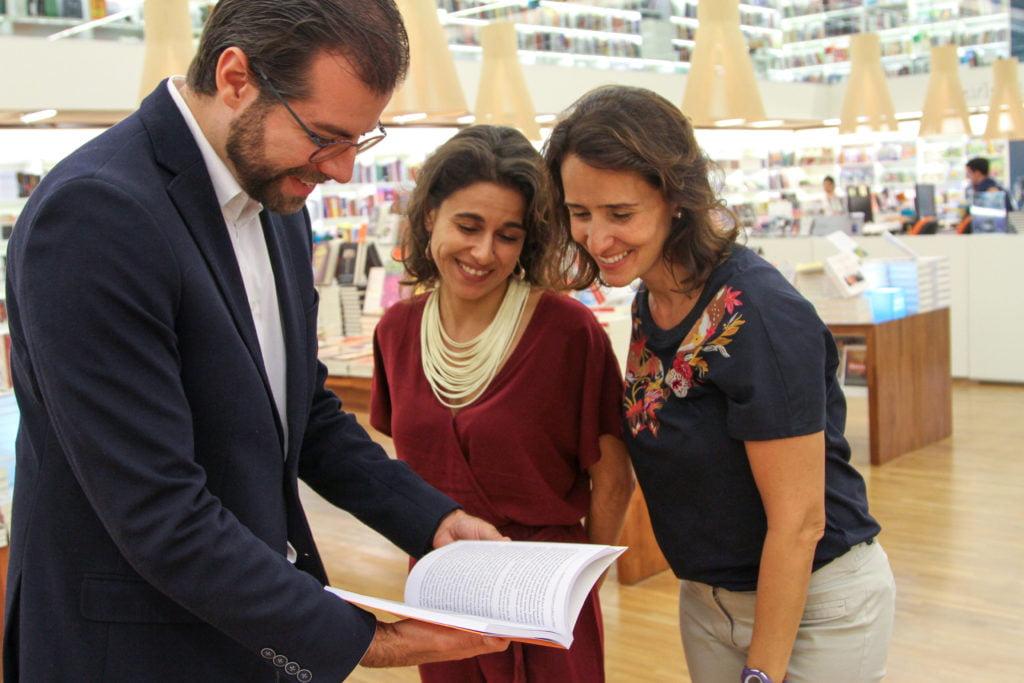 Equipe do Advocacy do Alana folheia o livro Autorregulação da Publicidade Infanatil no Brasil e no Mundo