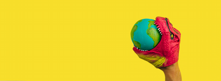yellow background with a plastic dinosaur toy eating a little planet Earth
